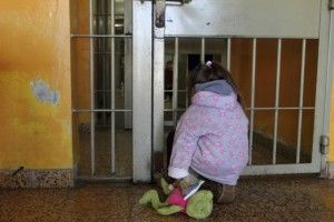 Four-year old Milagros peers at her mother Valeria Cigara (far inside the cell) in who is currently in prison awaiting trial for robbery, in Magdalena August 19, 2012. Picture taken August 19, 2012.