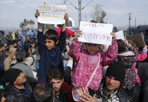 Migrant children hold posters as they block the railway track at the Greek-Macedonian border, near the village of Idomeni, Greece March 3, 2016. REUTERS/Marko Djurica