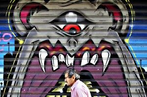 A man walks past graffiti painted on a closed shop at Monastiraki area in central Athens...A man walks past graffiti painted on a closed shop at Monastiraki area in central Athens, Greece, July 7, 2015. Greece faces a last chance to stay in the euro zone on Tuesday when Prime Minister Alexis Tsipras puts proposals to an emergency euro zone summit after Greek voters resoundingly rejected the austerity terms of a defunct bailout. REUTERS/Christian Hartmann