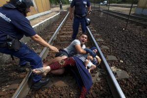 Hungarian policemen stand over a family of immigrants who threw themselves onto the track before they were detained at a railway station in the town of Bicske, Hungary, September 3, 2015. Reuters and The New York Times shared the Pulitzer Prize for breaking news photography for images of the migrant crisis in Europe and the Middle East. REUTERS/Laszlo Balogh      TPX IMAGES OF THE DAY      - RTX2AJJI