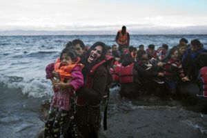 A refugee screams for help after she and her daughter fell in the water as they arrive along the northeastern Greek island of Lesbos,  Friday, Oct. 2 , 2015. The International Organization for Migration says a record number of people have crossed the Mediterranean into Europe this year. (AP Photo/Muhammed Muheisen)