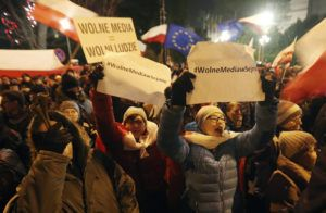 Warsaw residents have gathered for a civic protest outside the Parliament building in Warsaw, Poland, on Friday, 16 December 2016, in support of opposition lawmakers who were blocking the podium in protest against ruling party's plans to limit media access to lawmakers.(AP Photo/Czarek Sokolowski)