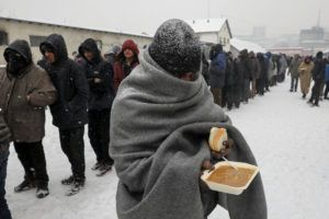 A migrant carries a plate of free food during a snowfall outside a derelict customs warehouse in Belgrade, Serbia, January 11, 2017. REUTERS/Marko Djurica
