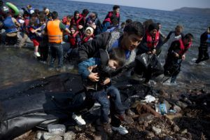 Afghan migrants arrive on the shores of the Greek island of Lesbos after crossing the Aegean Sea from Turkey on a inflatable dinghy, Monday, Sept. 21, 2015. Greece's coast guard was searching Sunday for 26 migrants missing off the coast of the eastern Aegean island of Lesbos after the boat they were traveling in sank. (AP Photo/Petros Giannakouris)