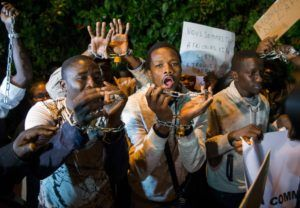 """Protesters, some from Sub-Saharan African nations, shout slogans during a demonstraion against """"Slavery in Libya"""" on November 23, 2017, outside the Libyan embassy in the Moroccan capital Rabat. / AFP PHOTO / FADEL SENNA"""