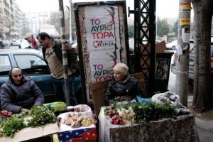 Elderly women sell vegetables in front of SYRIZA pre-election campaign posters outside Kapani market in Thessaloniki, Greece on January 20, 2015.